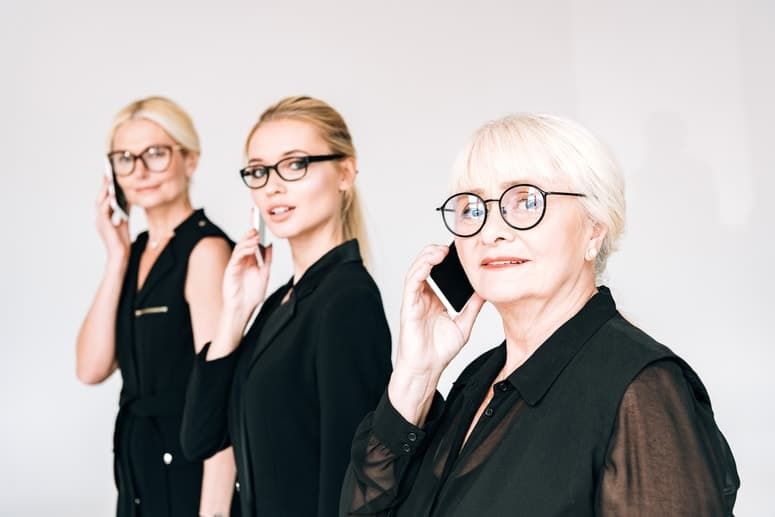 3 women holding phones to their ears